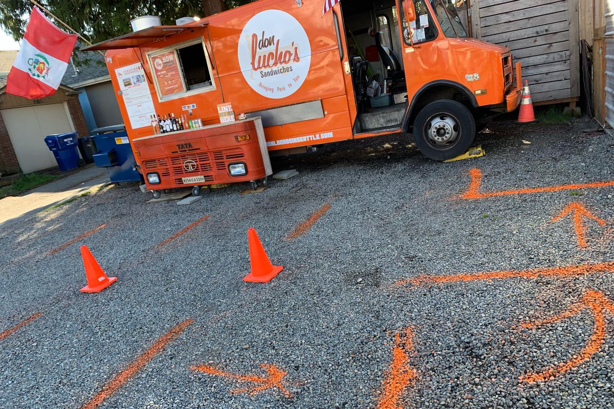 The orange food truck of Don Lucho's in a parking lot with orange painted lines