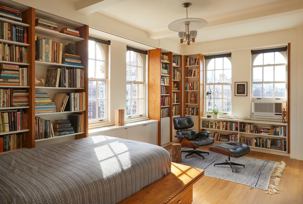 A bedroom. There is a bed on a wooden bed frame. There are multiple bookshelves full of books. There are four windows looking out onto a cityscape. There is a black leather lounge chair and footrest.