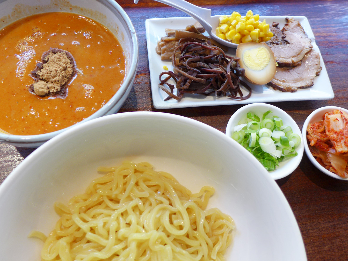 A bowl of noodles with broth and fixings to dip in