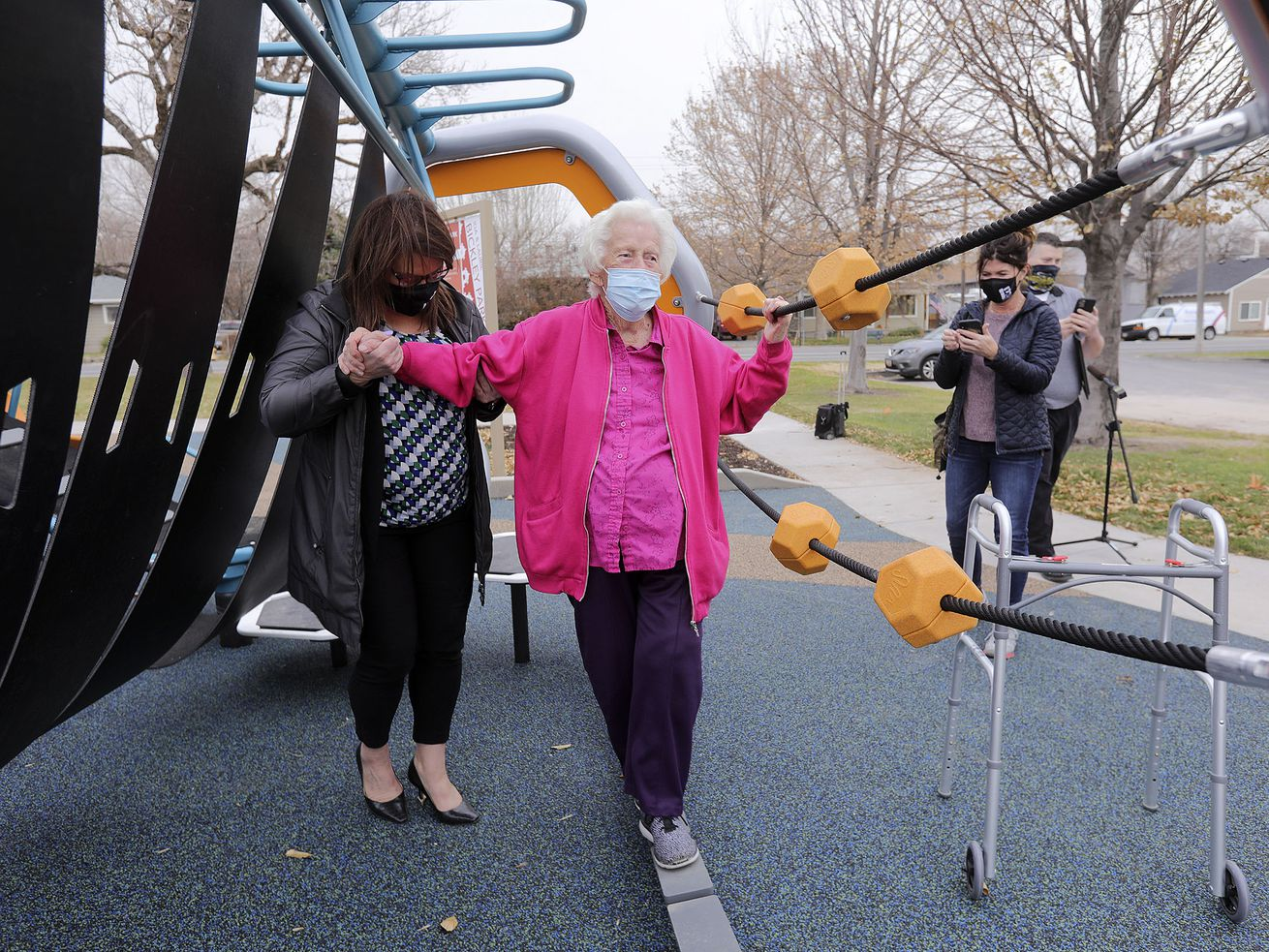 South Salt Lake Mayor Sherie Wood helps Ida Brickley,  94, balance and walk on a suspended bridge on a Hedra Playground structure at the Ida and Laurie Brickley Park adjacent to the Columbus Center in South Salt Lake on Wednesday, Nov. 18, 2020. Construction of the all abilities park was just completed and was named in honor of Ida and her daughter, Laurie, who have been volunteering at the Columbus Center Library three days a week for 13 years. The playground equipment is designed for all ages and accommodate those with physical, sensory and intellectual disabilities.