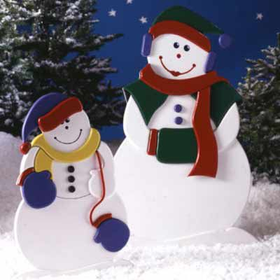 A wooden Christmas yard decoration with two smiling snowmen wearing scarves.