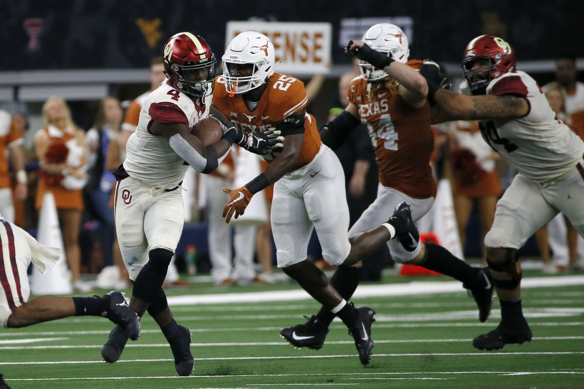Oklahoma running back Trey Sermon (4) tries to avoid a tackle by Texas safety B.J. Foster during a Big 12 title game in 2018.