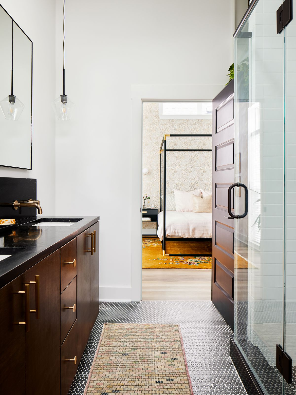 A bathroom with dark colored wooden cabinetry. The floor tiles are black and the walls are painted white. There is a glass light fixture.