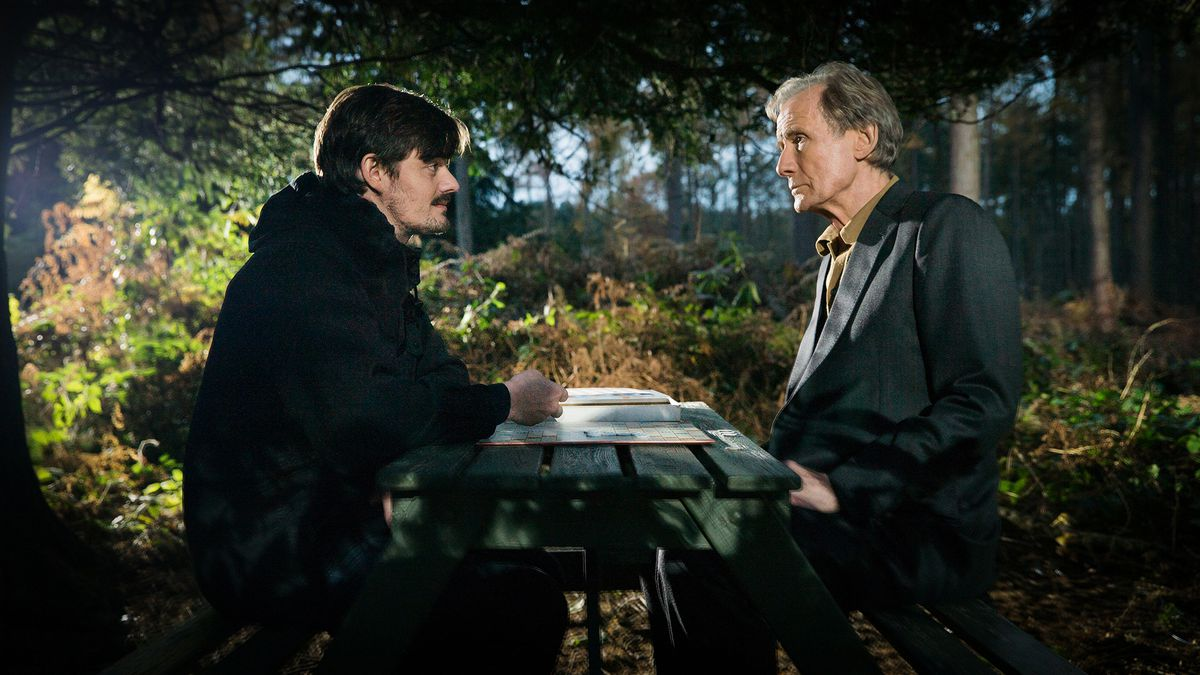 sam riley and bill nighy sit across from each other
