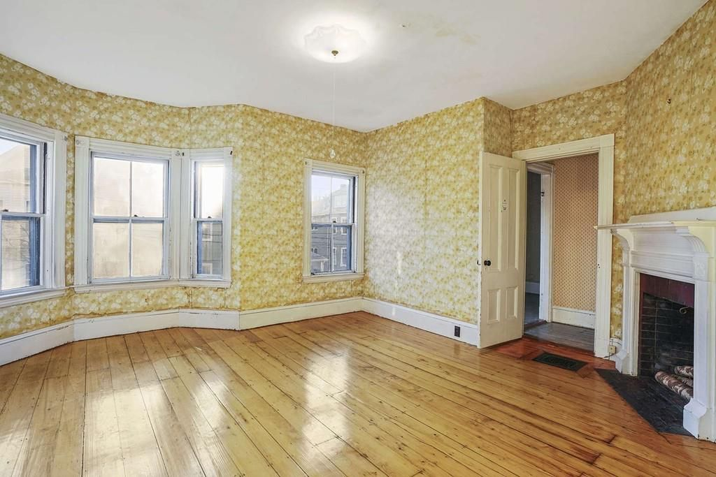 An empty bedroom with a bay window and a fireplace.