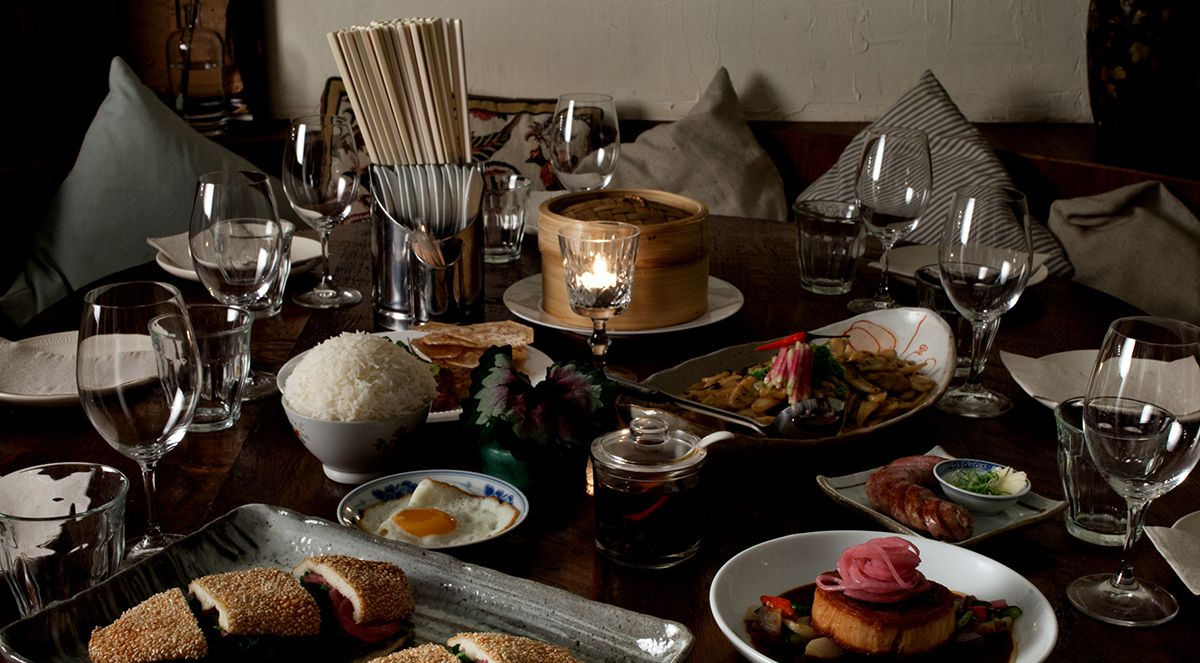 A candlelit dinner table filled with dishes, a heap of white rice, a fried egg, sliced sandwiches, a bamboo steamer basket, and glassware