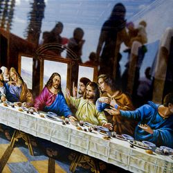 """People are reflected in the glass of a framed depiction of """"The Last Supper"""" as they browse the shops and booths Sunday at the Swap Meet in West Valley City. The swap meet is held on Saturdays and Sundays."""