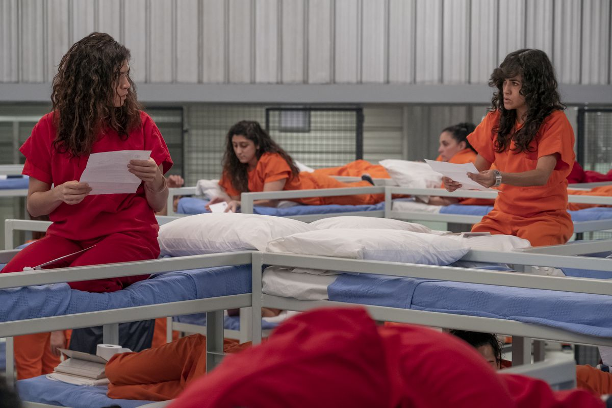 Inmates within an dramatized ICE detention facility on bunk beds talking.