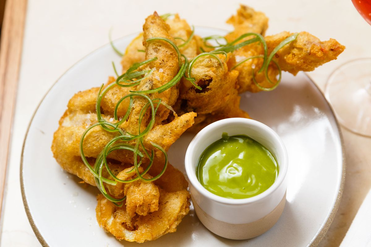 A golden fried crab topped with green garnishes sits next to a cup of green sauce on a white plate