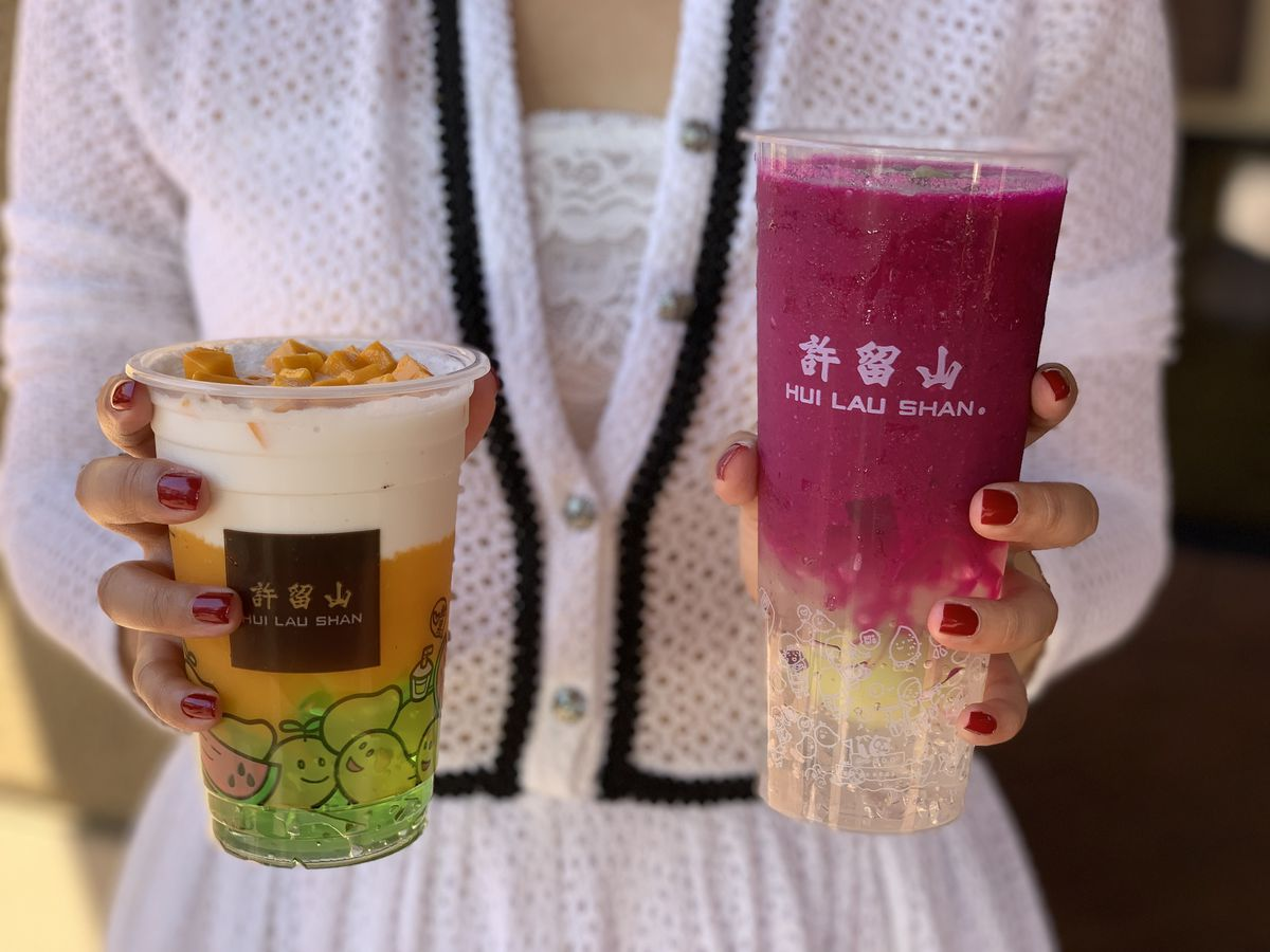 A person holds two plastic cups of slushie, one with mango and coconut and the other with purple dragon fruit.