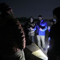 Adam Billings, Utah Schools for the Deaf and the Blind director of deaf outreach and online programs, troubleshoots as students and faculty from the school get some help from students and faculty from Colorado's Platte Canyon High School putting their handmade boat together after dark on Lone Rock Beach at Lake Powell on Friday, March 26, 2021. The Platte Canyon High School Yacht Club previously built a similar boat and helped mentor the Utah Schools for the Deaf and the Blind Yacht Club. Both clubs are training for the SEVENTY48, a 70-mile human-powered boat race from Tacoma to Port Townsend, Wash.