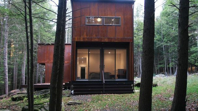 A narrow wooden house in a forest.