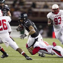 Hawaii wide receiver Jeremiah Ostrowski, center, gets pulled down by Lamar defensive back Tyrus McGlothen during the second quarter of the NCAA game between the Lamar and Hawaii, Sept. 15, 2012 in Honolulu.