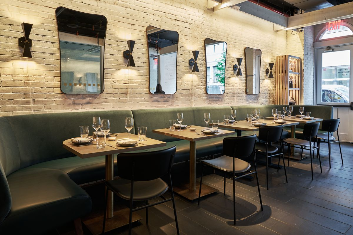 Tables set next to a light blue banquette and a white exposed brick wall behind it with mirrors