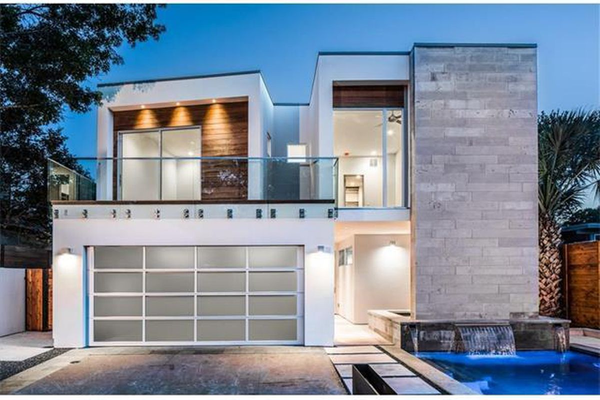 Two-story contemporary with concrete, stucco, and glass facades, including garage door