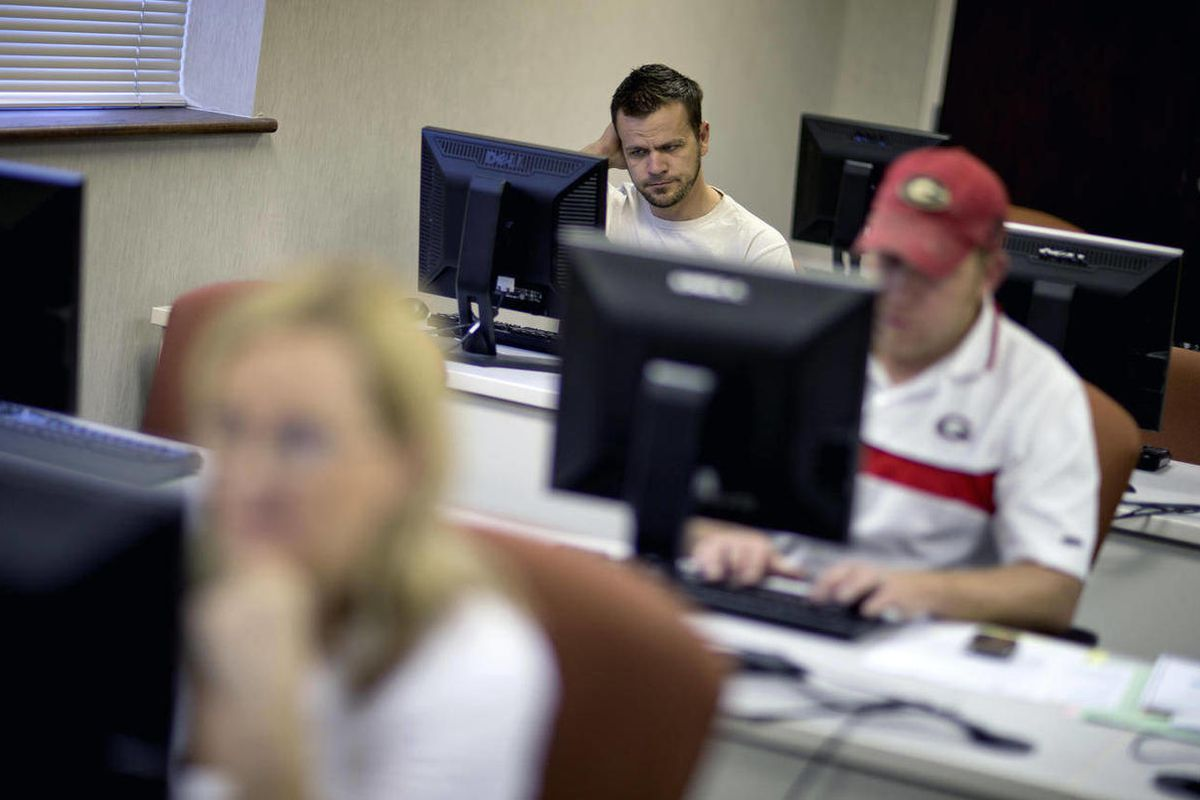 In this Aug. 22, 2012 file photo, Scott Marshall, top, of Calhoun, Ga., files for unemployment, in Dalton, Ga. Fewer Americans applied for unemployment benefits last week, and a private survey showed businesses stepped up hiring in August. The data sketch