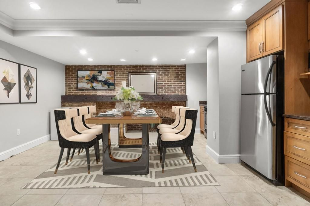 A dining room with a table and chairs next to a large fridge.