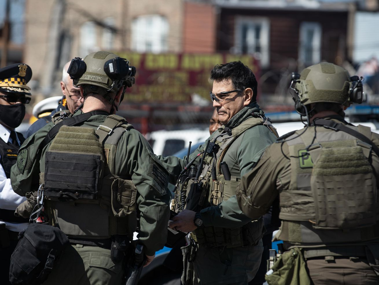 SWAT teams and a police officer talk at an active shooter scene near 207 N. La Crosse Ave. in the South Austin neighborhood on Saturday.