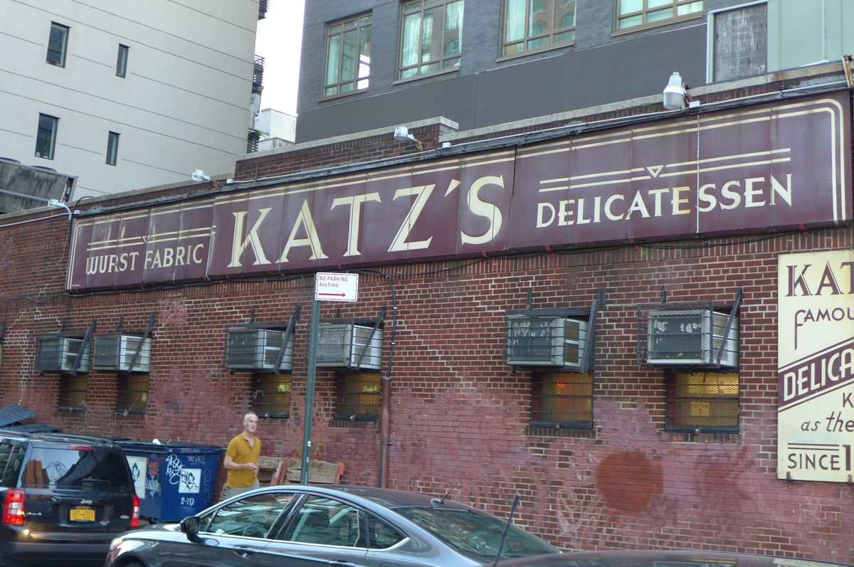 """The side of Katz's is dominated by a very old brown sign that says """"delicatessen"""" and """"wurst fabric""""..."""