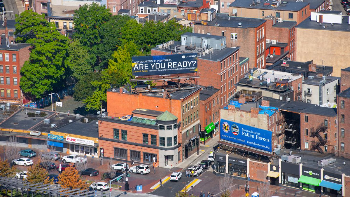 """Aerial view of a building in a city with a billboard on top that reads, """"Are you ready?""""."""
