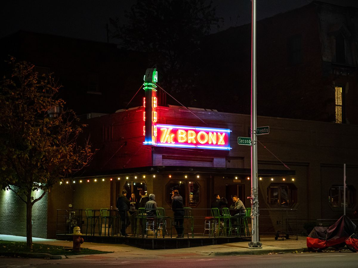 The Bronx shown at night with customers gathered on the smoking patio at the corner.
