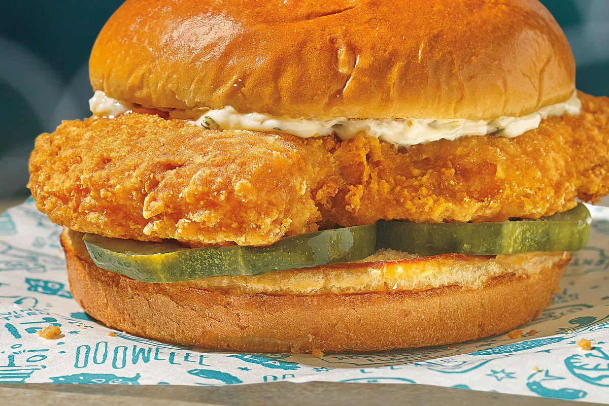 A fried fish fillet on a bun with pickles and tartar sauce