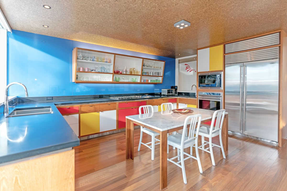 A bright kitchen has blue walls and counters with yellow, white, and red cabinets.