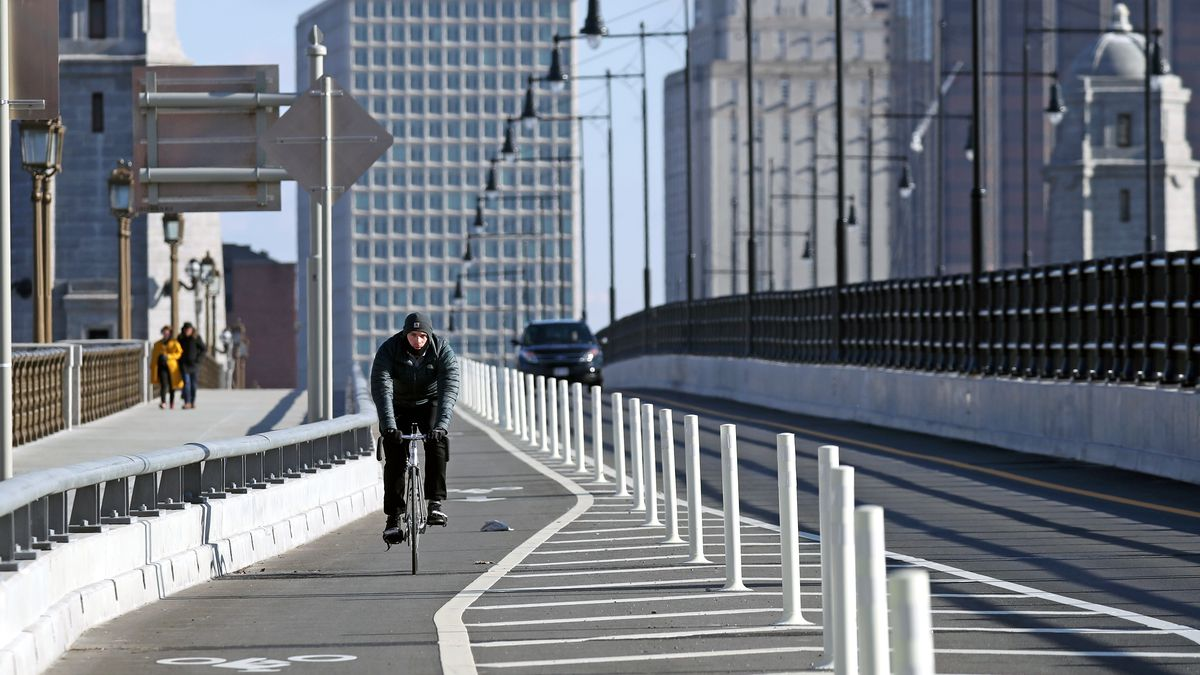 A lone bicyclist riding in a protected bike lane on a bridge and there are buildings in the background.