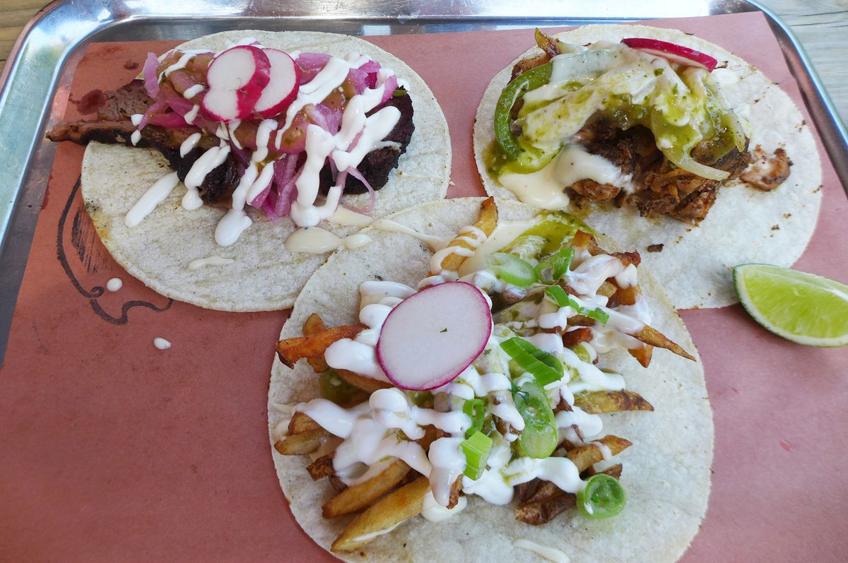Three tacos on flattened tortillas on brown paper on a metal tray.
