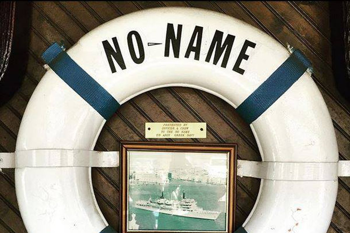 """A buoy with the words """"No Name"""" and a photograph of a boat adorn a wall at No Name Restaurant"""