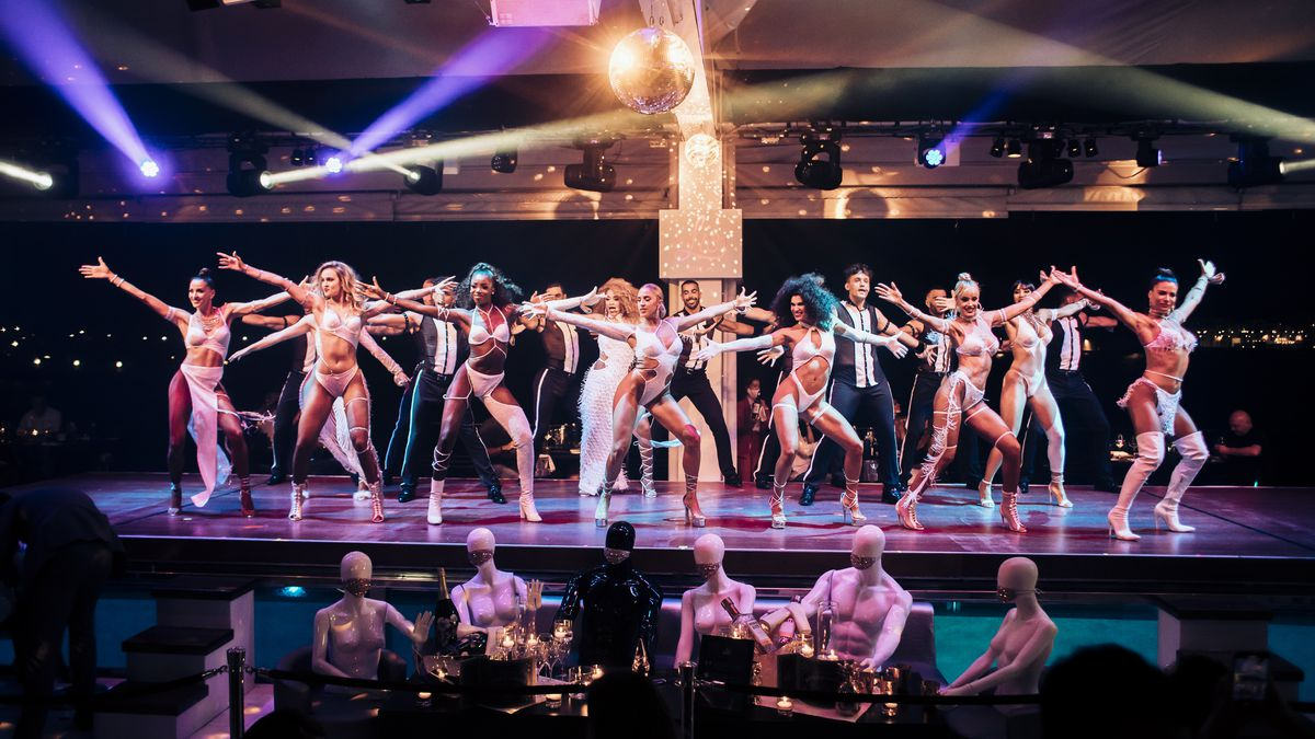 A group of dancers on a stage with mannequins in a row in front of them.
