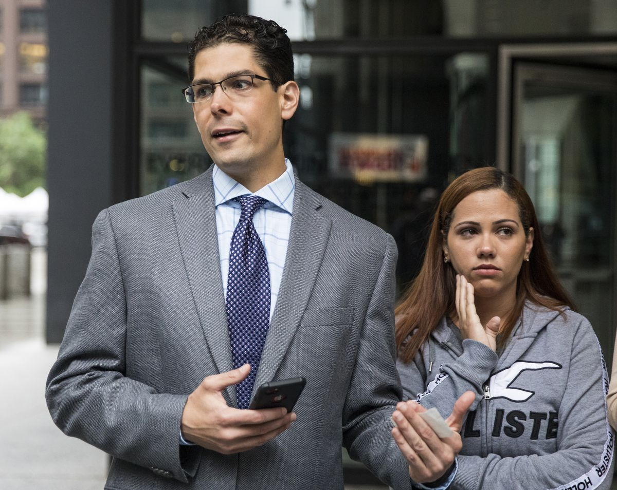 Lidia Karine Souza, a migrant from Brazil who was separated from her 9-year-old son Diogo shortly after entering the United States, listens as her attorney Jesse Bless (left) speaks with reporters during a press conference outside the Dirksen Federal Cour