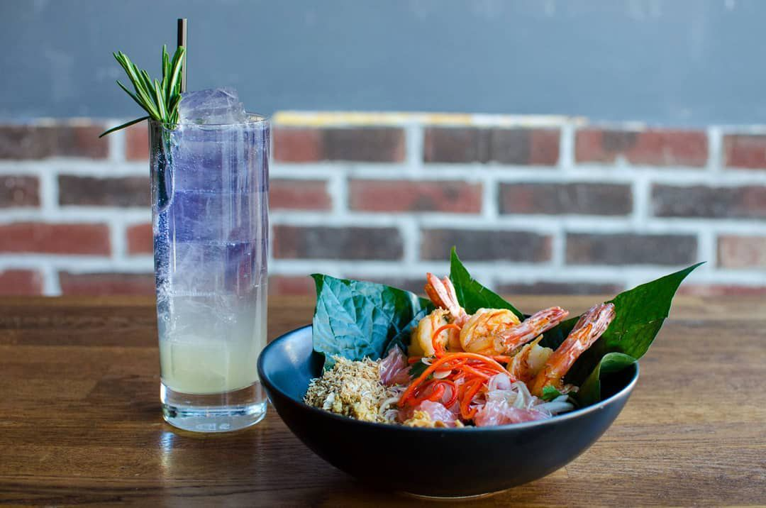 A drink and bowl of food sit on a wooden table in front of a brick wall. The drink, served in a tall, thin glass with ice, is white-ish near the bottom and purple at the top, garnished with a sprig of rosemary. The bowl is full of a citrus salad with shrimp and betel leaves.