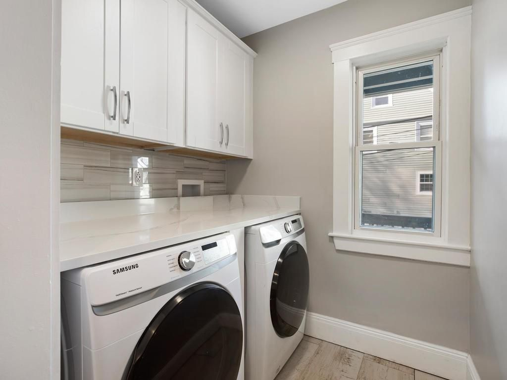 A small laundry room with a side-by-side washer-dryer under a counter.