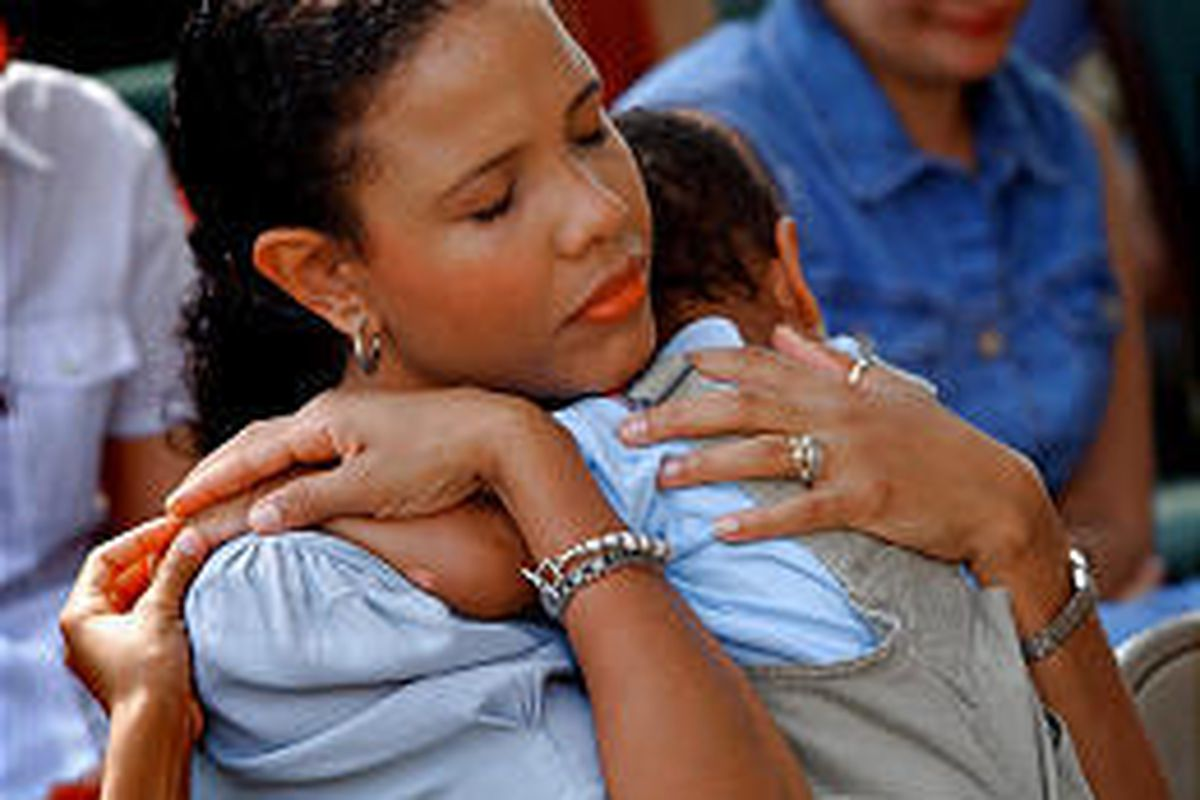 Sindy Jessup holds her son, David, and touches her daughter's hand at outdoor church service in Virginia Beach.