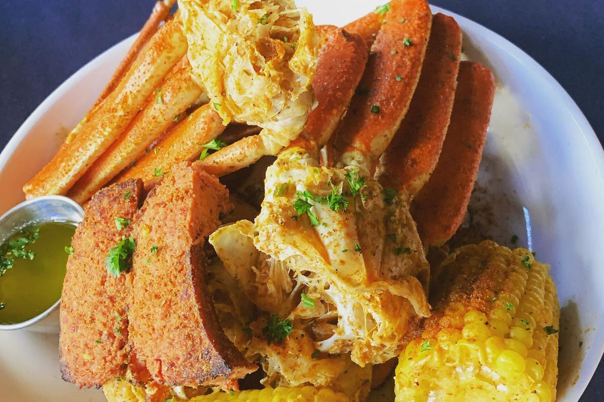 A plate of crab legs, butter, and corn on the cob from Sweet Auburn Seafood