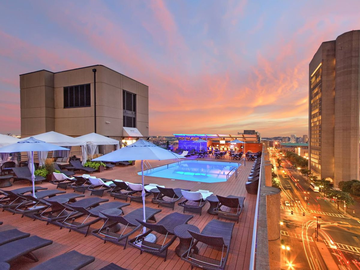 A hotel rooftop pool is photographed at sunset, with city skyline views