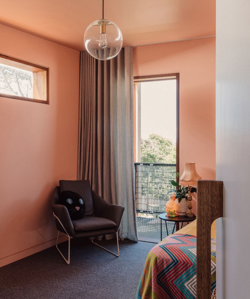 A bedroom with peach-colored walls and a window.