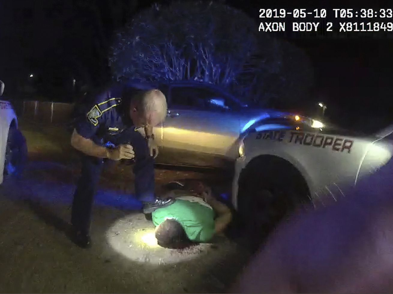 This image from video from Louisiana state police state trooper Dakota DeMoss' body-worn camera, shows trooper Kory York bending over with his foot on Ronald Greene's shoulder after he was taken into custody on May 10, 2019, outside of Monroe, La.