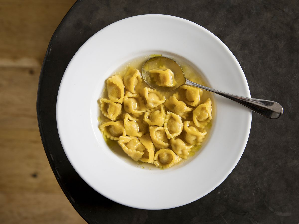 Agnolotti in broth in a white bowl on a black table