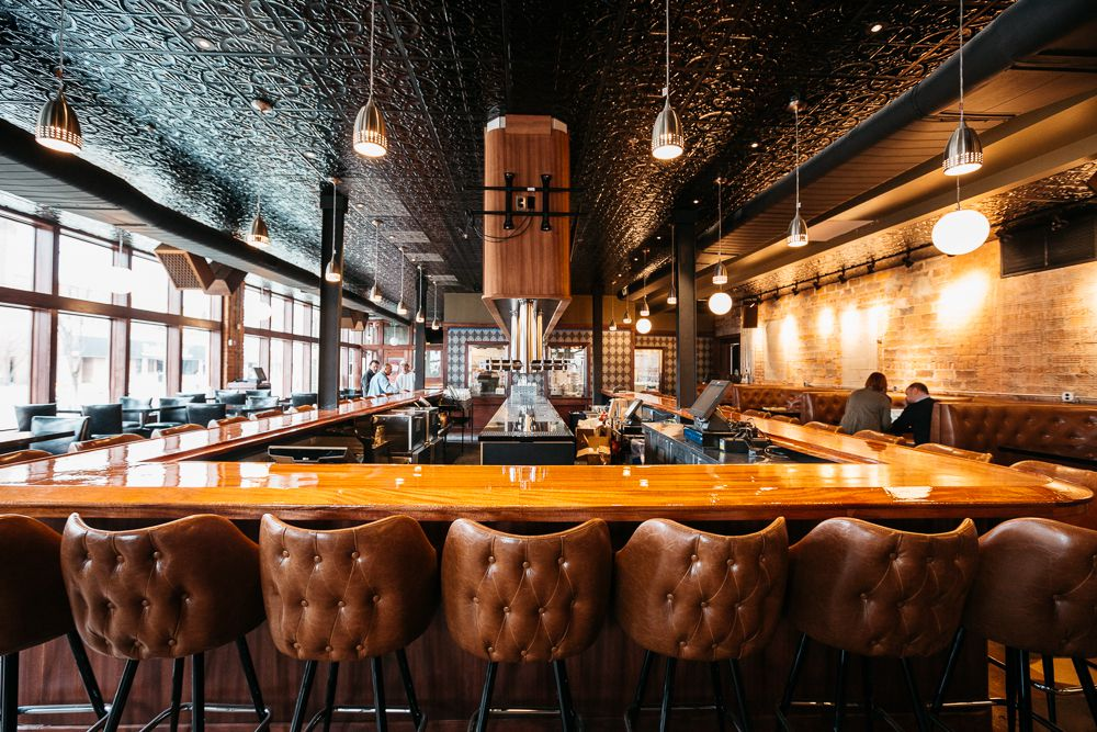 Brown upholstered leather bar chairs surrounding a rectangular bar at HopCat in Detroit.