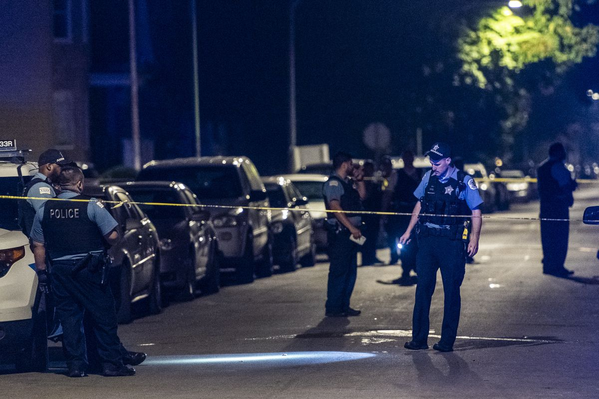 Police investigate the scene where a woman was shot Sunday morning in the 1300 block of West 73rd Street.   Tyler LaRiviere/Sun-Times