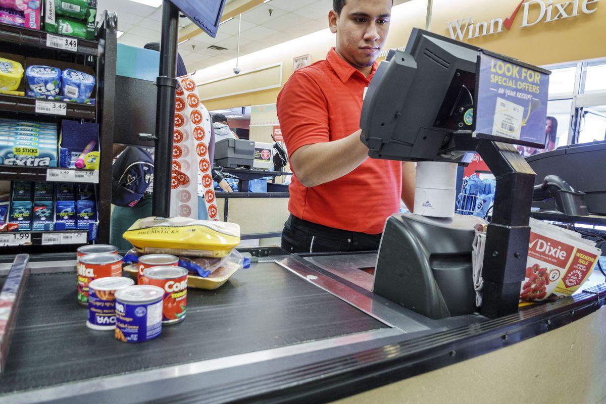 Man works at a cash register in a supermarket checkout line.