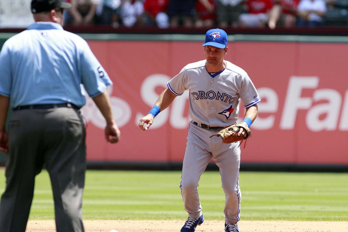 May 27, 2012; Arlington, TX, USA; Toronto Blue Jays second baseman Omar Vizquel (17) retrieves a ball for a fielders choice during the first inning of the game against the Texas Rangers at Rangers Ballpark. Mandatory Credit: Tim Heitman-US PRESSWIRE