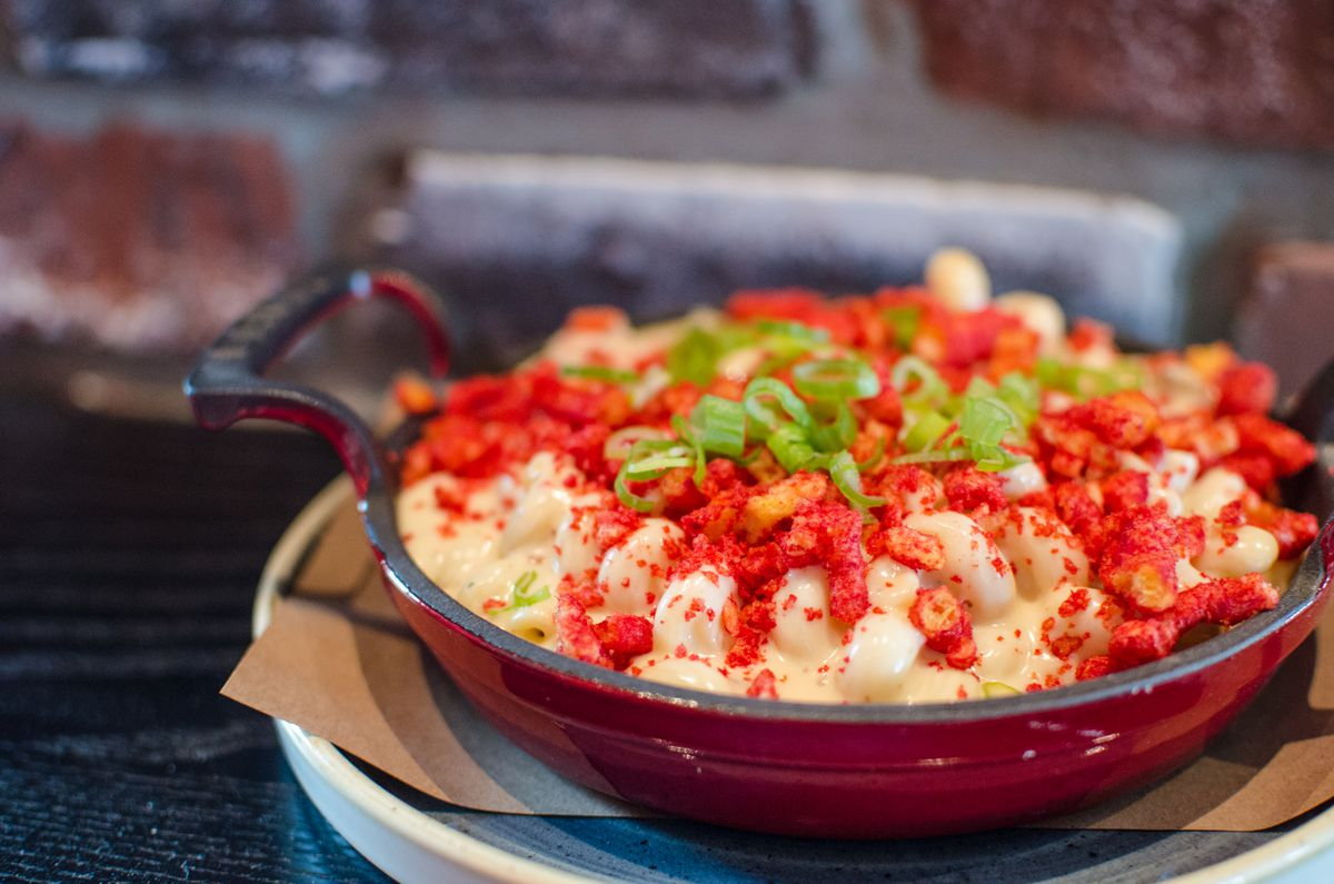 A creamy mac and cheese topped with bright red Flamin' Hot Cheeto dust and chopped scallions is served in a cast iron pan. It sits on a dark wooden table in front of a brick wall.
