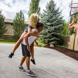 Kurt Christensen gets blocked by his daughter, McCall, 18, left, while his other daughter, Elle, 13, takes a shot during a game of basketball at their home in Cottonwood Heights on Wednesday, Aug. 12, 2015.