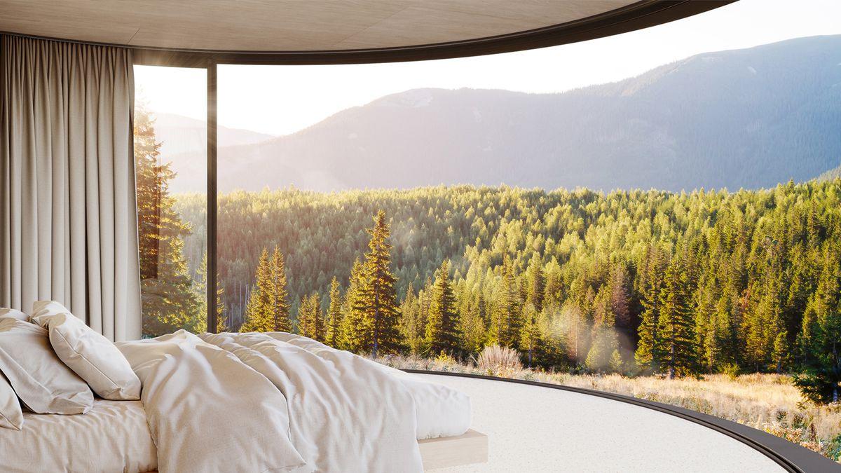 Bed in room overlooking woods