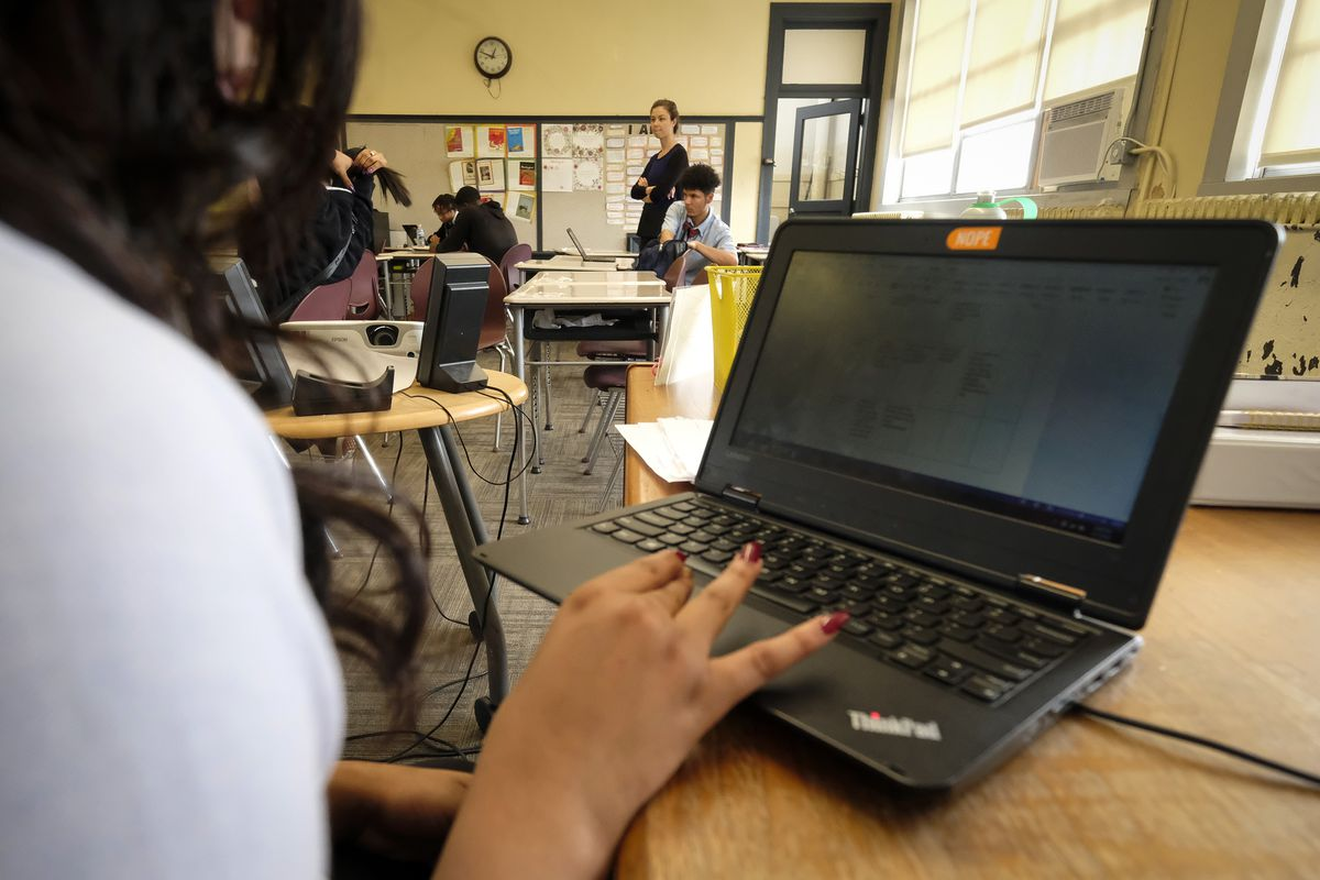 A female student in a classroom uses a laptop computer, with other people in the background.