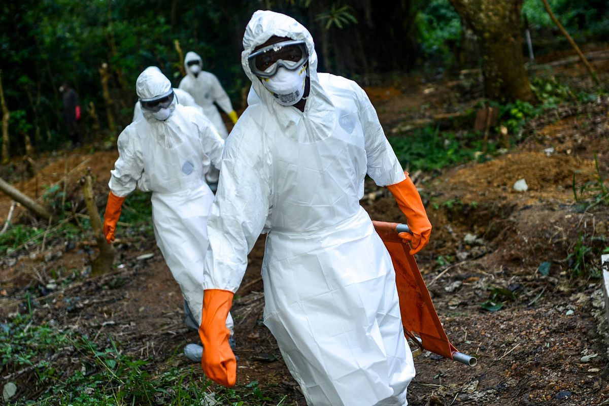 Members of a volunteer medical team wear special uniforms for the burial of 7 people, sterilized after dying due to the Ebola virus, in Kptema graveyard in Kenema, Sierra Leone on August 26, 2014.