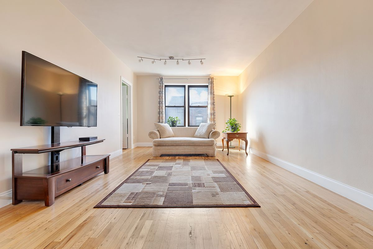 A living area with hardwood floors, beige walls, two windows, and a TV on a wooden stand.